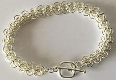 This pretty design is made of a 2 row patten, first row has just 2 jump rings the second 4 jump rings. Alternating the entire length making this patten. I have used 6mm Silver Plate Jump Rings in this design, each jump ring has to be opened and carefully closed in its place in the patten.  Chain Maille has come a long way since those knights of old. There are now so many pattens and designs the story of each can be traced back to one of those historic maille families. This bracelet is…
