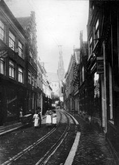 De Damstraat in Haarlem, met tramrails en links de sigarenfabriek van Hilarius, ca. 1890.
