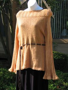 This sweater is worked in the round with very little seaming. The tunic has side slits for ease in the hips and a cinched waist for a flattering hourglass shape. The ribbed sleeves are stretchy and have pretty belled cuffs. The off the shoulder neckline is a turned down ribbing to match the sleeves. Worked up in sumptuous alpaca yarn with gorgeous, this is a simple sweater to make and a favoriate to wear.