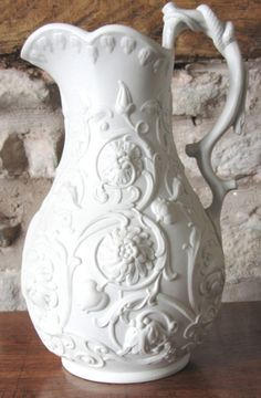 WHITE RELIEF MOULDED STONEWARE JUG