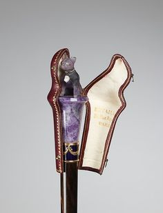 Custom amethyst pug knob on end of parasol (1900-1910) with its own protective cover. From the MET collection.
