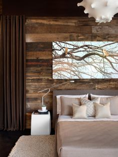 "In any space with a strong decorative style, you can avoid creating a ""theme"" room by incorporating unexpected, contrasting elements, as designer Michael Habachy did in this striking retreat. ""One of the best ways to create warmth in a modern room is by adding texture,"" he says. ""For this bedroom design, I added the unexpected by contrasting rustic reclaimed wood as a backdrop for this sleek contemporary furniture."""