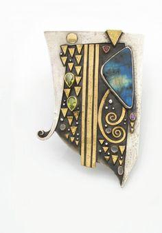 """Linda ladurner.pendentif broche """"le chant d'orphée"""".en argent noirci et martelé et motifs d'or jaune appliqués, de forme asymétrique agrémenté d'une plaque polie de labradorite et de pierres fines cabochons et facettées..retenu par un cordon de soie ponctué de perles de bois..signé..poids : 62,8 g (l'épingle en métal).dim. 10,4 x 7,2 environ"""