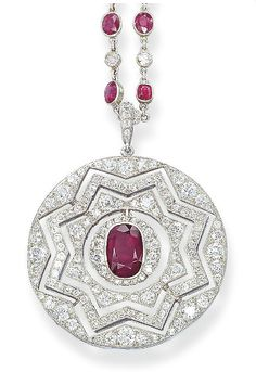 A VERSATILE ART DECO RUBY AND DIAMOND PENDENT SAUTOIR   The openwork circular pendant of star motifs, either entirely set with diamonds or with a reversible calibré-cut ruby star, centering upon an oval-shaped ruby within a pavé-set diamond surround, to the spectacle-set ruby and diamond neckchain, mounted in platinum, circa 1930, chain 86.0 cm long, pendant 5.5 cm long