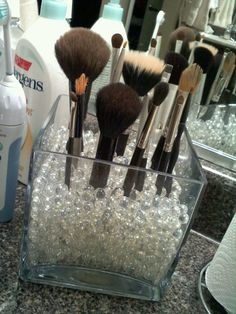 Glass beads in a square vase to hold makeup brushes. Great idea!