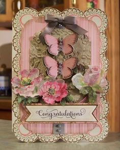 Congratulations Anniversary or Wedding Card. The card was made using mostly Anna Griffin card stocks and dimensional embellishments. Several layers are dry embossed and the roses are adorned with dazzling details glitter. The butterflies are adorned with gray pearls and the next two layers are embossed and lightly sponged to give them a nice vintage look. The card is hand cut around the scallops, both inside and outside.