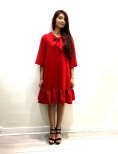 Petite robe rouge avec volants et noeud, manches 3/4, longueur au genou.