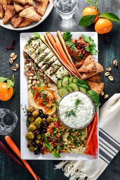 Mezze Party Platter. Loaded up with hummus, baba ganoush, marinated feta, tzatziki, tomato rice salad, muhammara, za'atar pita chips, sliced veggies, and nuts, this platter is the perfect spread of Mediterranean and Middle Eastern flavors.   hostthetoast.com