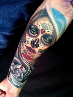 Very detailed mexican tattoo on man's forearm with love and rose symbols