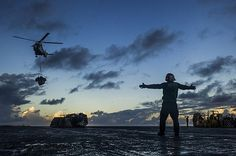 A Sailor aboard the aircraft carrier USS George Washington signals the pilot of an Puma helicopter from the Military Sealift Command as it delivers supplies to the ship's flight deck during a replenishment-at-sea