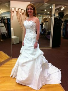 It is a pale ivory, strapless, A line dress, with a crumb-catcher top, asymmetrical bow bodice and pick-ups long the bottom. It has a medium length train and covered buttons down the back. Its Light w