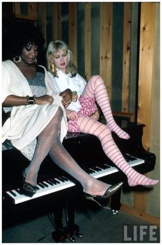(L-R) Singers Patti LaBelle and Cyndi Lauper sitting on piano 1996 Ann Clifford