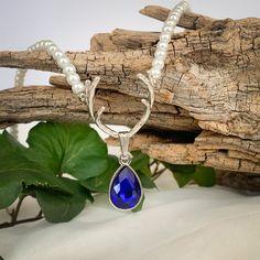 Perfekt zum Dirndl - Perlenkette mit Hirschgeweih und Tropfen. Perlenkette mit verschiedenfarbigen Tropfen erhältlich #trachtenlook #trachtenschmuck #hirsch #perlenkette #perlenschmuck #perlen #blau #hirschgeweih #tropfen #glasstein #schmuckstein #dirndlkette #kettezumdirndl Deer Horns, Gemstones, String Of Pearls, Pearl Jewelry, Blue