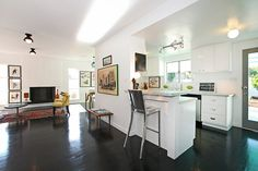 Open floor plan kitchen; simple cabinets, built in bar and stools