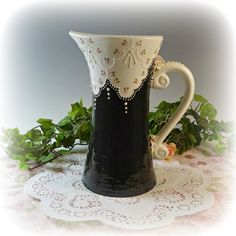 This wonderful pitcher is as useful as it is pretty! It easily holds 44 ounces making it a great serving piece for any occasion. Done in rich black with wide luxurious lace work. Within this lacework are pink rosebuds white at the handle, both top and bottom, are delicate pink handmade roses, leaves and flowers. Stunning!FEATURES:♥ Delicate handmade flowers and leaves.♥ Intricate lacework in dimensional glaze.♥ Multiple coats of color glaze are carefully applied, then finished with two coats…