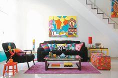 O visual desta sala de estar não fica pesado graças à base neutra: paredes brancas e estofados pretos. Baú, almofadas e pufes foram cobertos com tecidos de padronagens variadas. Seguir a mesma cartela cromática foi o segredo para acertar na combinação de estampas.