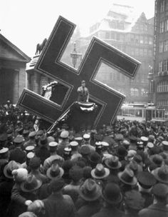 A Nazi leader in Hamburg, Germany, seen standing in front of a huge swastika in 1933. He was telling the assembled citizens that they must contribute to the Nazi charity Winter Help.