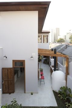 DEPOIS - A nova configuração do quintal mostra a parede do quarto (fundos) no segundo pavimento, com janelas laterais, voltadas para o pergolado que cobre o corredor com churrasqueira e forno de pizza. A cozinha também chegou até os limites do volume construído, desenhado pelo escritório SET Arquitetura, responsável pela reforma do sobrado no bairro da Liberdade, em São Paulo, originalmente construído na década de 1950