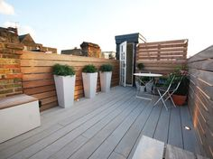 Battersea Roof - Really Nice Gardens.  These 3 large planters containing Choisya 'White Dazzler' give height and structure to the space.