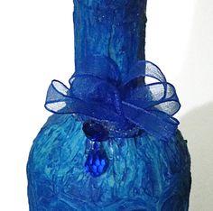 Garrafa texturizada azul royal, enfeitada com fita de organza, carreira de cristais, pedra azul e cristal em gota. R$18,00