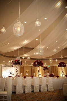 Ballroom turned into an elegant wedding reception using draping, lanterns, and elaborate floral elements.