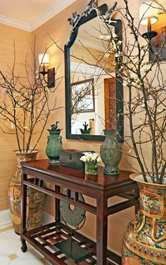 "Quince branches and Asian-inspired vases flank an antique Chinese console from the White Lotus Collection in Melissa Ziober and Noe Guerra's peaceful powder room. To maintain the historical home's integrity, the NXG Studio design team first restored the walls, moldings, and floor. ""The space is traditional while still feeling modern and fresh,"""