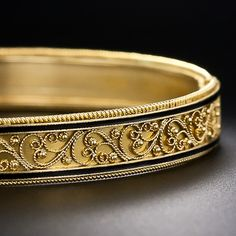 A classic Etruscan revival style hinged bangle bracelet by the justly acclaimed Italian jeweler - Castellani. The center of the bracelet is graced with a masterfully applied twisted wire and granulation design outlined on both sides with slender stripes of black enamel. For the finishing touch, the bangle is bordered with delicate golden rope. Italy, 15kt, circa 19th century
