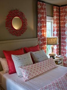 The hot coral hue of drapery fabric informed the room's color palette, with a collection of bold prints popping against neutral walls and carpeting.