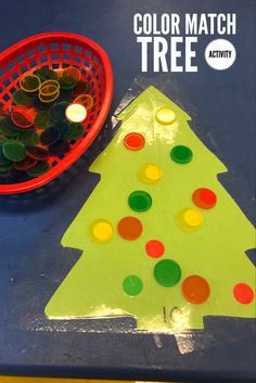 Kids make color match using color discs by placing on ornaments.