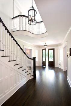 Grand formal foyer with dark hardwood floors and double front doors. Sweeping paneled staircase with white spindles and dark handrail. Curved balcony overlooking stairs, white walls and large glass and iron pendant.
