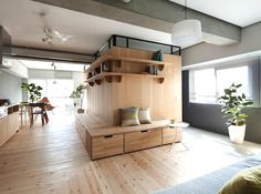 Sinato cleverly adds an L-shaped wood partition to expand a small apartment footprint in Japan