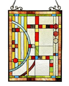 The Art & Craft Mission Circles Stained Glass Panel has a palette of reds, yellows, greens, blues, and browns in a geometrical design.