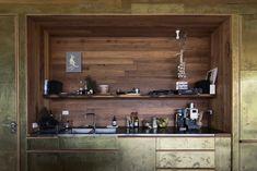 La cuisine intégrée dans un mur de rangements dorés