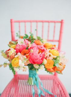 cheerful and bright wedding bouquet with pink peonies and yellow and coral ranunculus