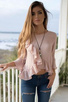 A blush top features 3/4 sleeves, ruffle overlap details, and no lining Material is Cotton