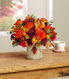 Bring that afternoon walk through the #fall forest in with this festive autumnal #arrangement! Glorious #OrangeRoses and golden blooms burst from a charming birch tree vase, adorned with a shimmering metal leaf on natural twine cord. Orange bi-color roses, orange #alstroemeria, orange #carnations, yellow button spray #chrysanthemums and burgundy cushion spray chrysanthemums are accented with parvifolia #eucalyptus. Delivered in Teleflora's #Autumn Colors Cylinder. Starts at $54.99