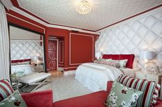 Effektvolle, weiße Polster-Paneele an der Wand eines roten Schlafzimmers