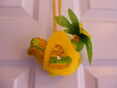 "This is a super cute bright yellow bird I made up from yellow felt and a soft suede like fabric in a yellow and green design.     She is about 5"" long by 3.5"" tall.    Her main colours are yellow and green. Her wings are decorated with green and clear acrylic gems. She has a bright yellow ribbon hanger.     Her eyes are green buttons    I gave her a tail made from artificial leaves and flowers in yellow and green with a bright yellow bead center.     She is not a toy and should not be…"