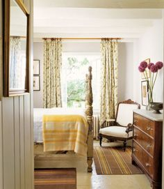 A carved bed is accented with tarnished gilding, while yellow-rose curtains dress the window's frame. Amish rag runners atop painted floors weave in additional colors and pale gray walls serve as a foil for brighter hues.