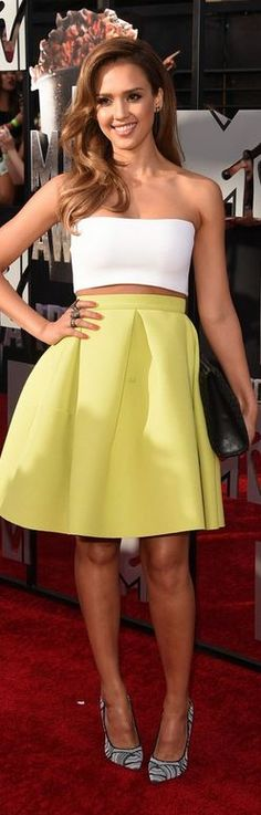 Who made  Jessica Alba's yellow pleated skirt, jewelry, black clutch handbag, gray print pumps, and white strapless top?