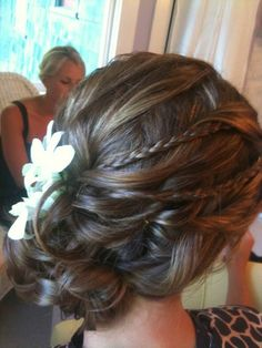 Updo with small braids, curls, and a flower accessory.
