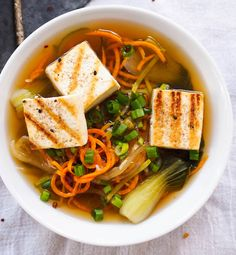 This Asian vegetable noodle soup with tofu uses spiralized zucchini and sweet potatoes in place of noodles to make a tasty, veggie packed, gluten free soup!