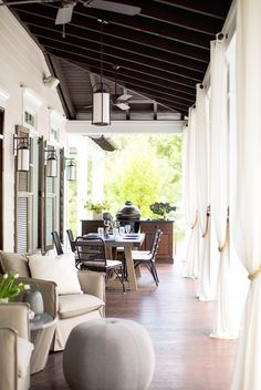 Outdoor dining area with neutral drapes and chairs.