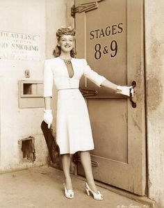 Ann Savage, looking 1940s super chic in her suit dress, white gloves, and sling-back shoes.