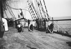 "Crew of the Pamir scraping the deck.   It is not the famous ""Holy Stone"" being used, but some iron tools."