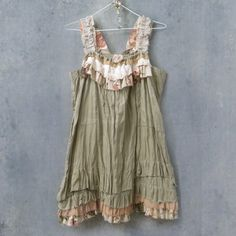 ruffled neckline, straps and hemline of linen, rayon, laces, and cotton with raw edges, in brown and green earth tones and florals and lots of hand stitching. Reconstructed upcycled from vintage and salvaged materials.