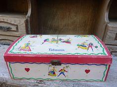 """קופסה העשויה מקרטון מצוירת ברקדנים עליזים צבעוניים מקסימה בייחודה קרועה בכמה מקומות יש לה סוגר מתכתי אך ללא מנעול  מכילה חוטי תפירה אורך: 31 ס""""מ רוחב: 21 ס""""מ גובה: 7.5 ס""""מ"""