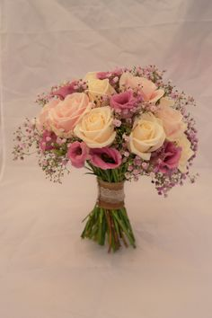 Hand tied bridal bouquet including pink Gypsophilia, Avalanche and Sweet Avalanche roses and pink lizianthus.