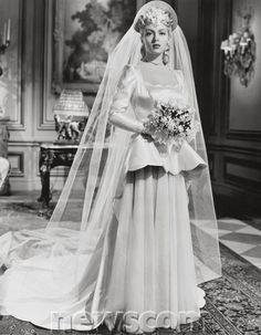 MARRIAGE IS A PRIVATE AFFAIR (1944) starring Lana Turner. A classic example of 1940s wedding gowns: heavy satin gown with a train, a halo 'crown' and long veil, long sleeves and a peplem. This gown has scalloping around the peplum and neckline.