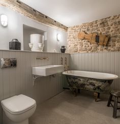 Miner's Cottage II - master bathroom in an eighteenth century renovated cottage with tongue and groove panelling, exposed stone and polished concrete floors. Fixtures include reclaimed cast iron bath and sink and exposed copper pipework taps